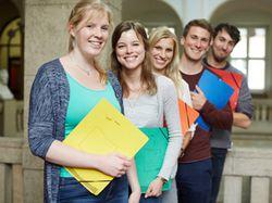 Fünf junge Menschen mit Mappen unter dem Arm lächeln in die Kamera