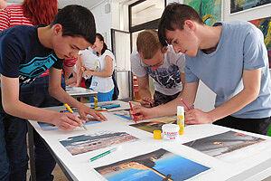 Schüler kleben Fotos auf einen Bogen Papier
