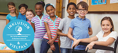 Mädchen und Jungen im Teenager-Alter stehen hintereinander in einem Klassenzimmer, ein Mädchen sitzt in einem Rollstuhl. Davor ein blauer Kreis mit Schrift zum Jahresmotto