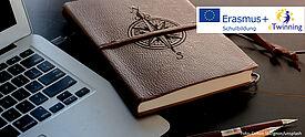 Symbolbild: Laptop und ledergebundenes Notizbuch