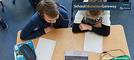 Zwei Schüler sitzen gemeinsam vor einem Laptop