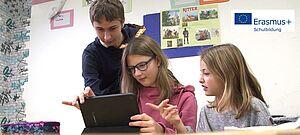 Ein Schüler zeigt zwei jüngeren Schülerinnen etwas an einem Notebook. Blick ins Klassenzimmer