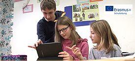 Ein Junge steht neben Schultisch, an dem zwei jüngere Mädchen an einem Notebook sitzen