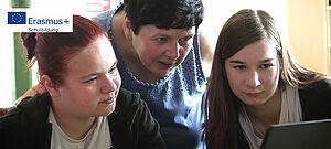 Zwei Mädchen vor Bildschirm. Lehrerin sieht ihnen über die Schulter.