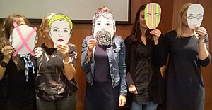 Fünf Schülerinnen stehen nebeneinander und halten Papiermasken in der Hand