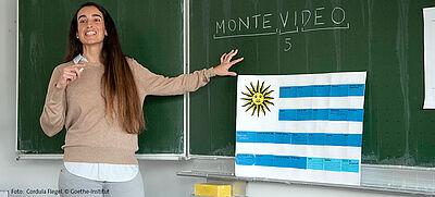 Lehrerin steht vor Tafel mit Flagge aus Uruguay