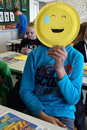 Schüler mit Pappteller vor dem Gesicht, der ein Smiley zeigt