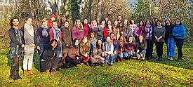 Grupppe Erwachsener steht auf Wiese vor Bäumen
