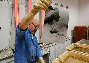 Mann in Labor hält ein Fotopapier in die Höhe