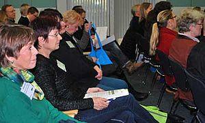 Menschen sitzen hintereinander auf Stühlen und hören einem Referenten zu