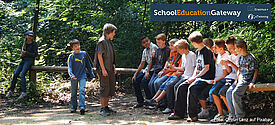 Jugendliche im Wald auf einem Baumstamm sitzend