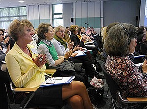 Frauen sitzen in Saal
