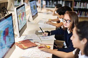 SchülerInnen vor Bildschirmen, die Weltkarten zeigen