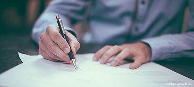 Person im Hemd unterschreibt Formular