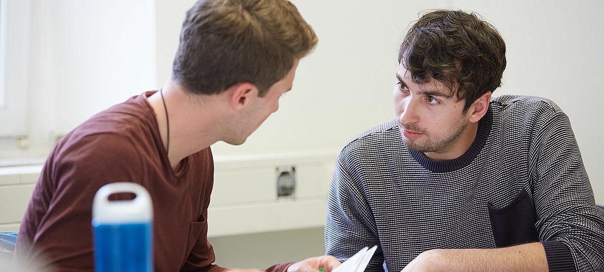 Zwei junge Lehrkräfte unterhalten sich miteinander