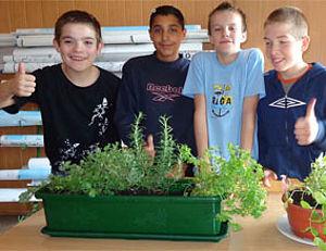 Kinder vor bepflanztem Blumenkasten