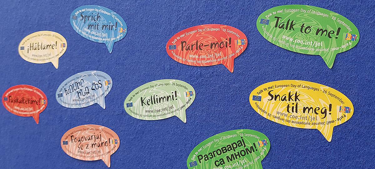 Sticker mit verschiedenen Sprachen auf blauem Hintergrund