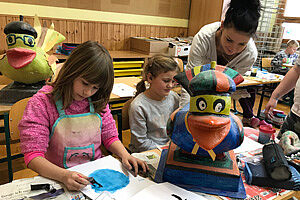 Zwei Kinder mit Lehrerin beim Werken mit Pappmachee