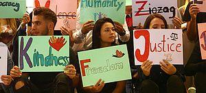 Jugendliche halten Schilder mit Aufschriften wie Freedom oder Justice