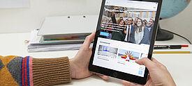 Hände halten Tablet mit PASCH-Website