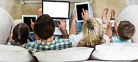 Zwei Erwachsene und zwei Kinder auf dem Sofa mit Tablets