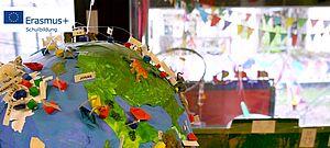 Globus mit aufgesteckten Gegenständen und Namensschildern im Gruppenraum der Kita