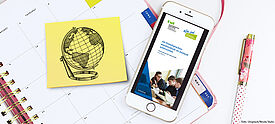Kalender mit Terminen zum FSA-Programm und Handy mit Fremdsprachenassistenz-Flyer auf dem Display - Symbolbild