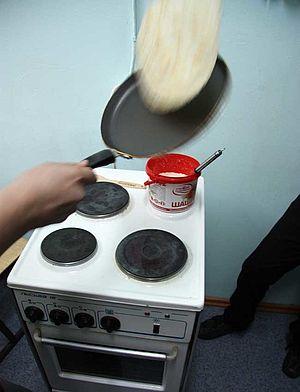 Ein Blini wird in der Pfanne gewendet.