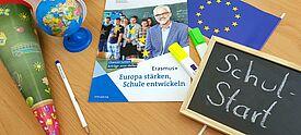 Collage aus Schultüte, Infoblatt, Globus und Tafel