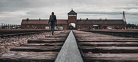 Junge Frau geht auf das Tor der Gedenkstätte Auschwitz-Birkenau zu