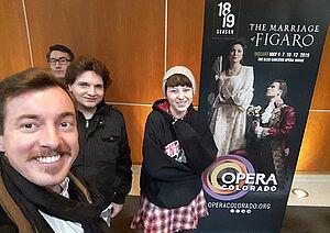Gruppe mit 4 Personen vor Werbeplakat für die Oper Figaro