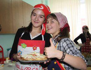 Zwei Mädchen freuen sich über ihr selbstgekochtes Essen.