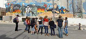 Jugendgruppe vor bemalter Mauer