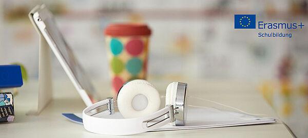 Notebook und Trinkbecher mit Kopfhörer auf Tisch