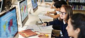 Schulkinder sitzen vor Computern mit Ansicht von Weltkarten