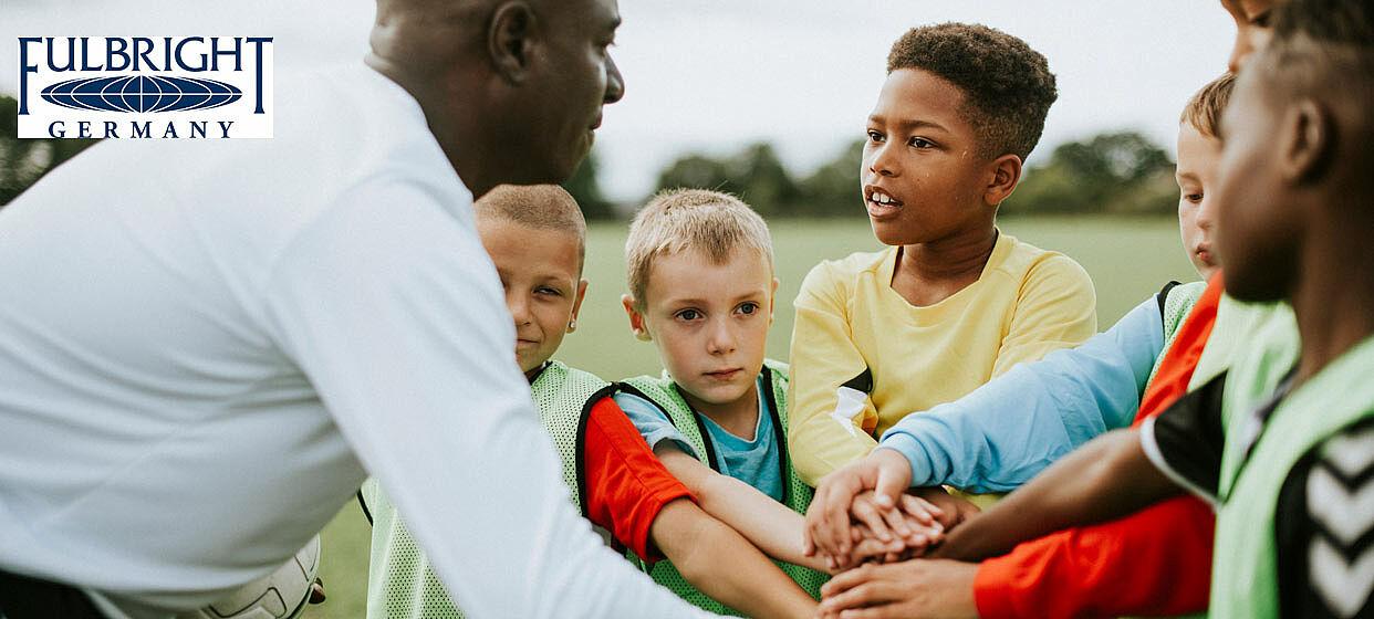 Lehrer mit dunkler Hautfarbe und Schüler mit heller und dunkler Hautfarbe bei der Begrüßung vor Fußballspiel