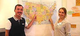 Zwei junge Erwachsene stehen vor einer USA-Karte