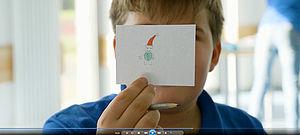 Kind mit Zeichnung eines Weihnachtsmannes vor dem Gesicht