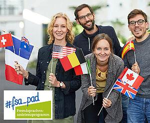 Vier junge Menschen mit Länderfähnchen machen Werbung für das Fremdsprachenassistenzprogramm