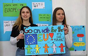 Zwei Schülerinnen zeigen Plakat