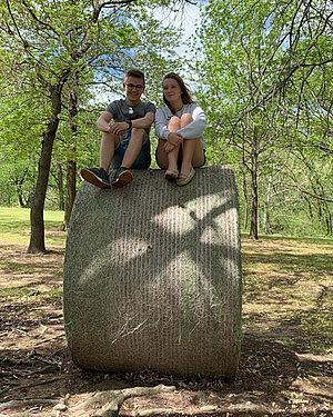 Zwei deutsch-amerikanische Austauschschüler sitzen auf einer Strohrolle unter Bäumen