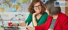 Zwei Frauen an Notebook vor Weltkarte