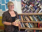 Frau vor Bücherschrank stehend