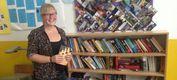 Frau steht vor Bücherregal