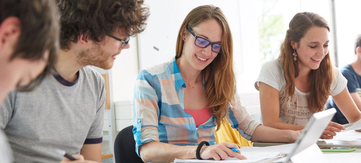 Junge Menschen an Schreibtisch mit Notebook