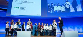 Schulklasse mit Moderator auf der Bühne