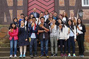 Gruppe von Jugendlichen vor einem Fachwerkhaus mit Brezeln in der Hand