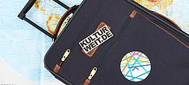 Blauer Rollkoffer mit kulturweit-Logo