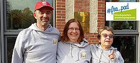 Ein Mann und zwei Frauen vor Gebäude