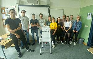 11 Jugendliche mit Wahlurne im Klassenraum